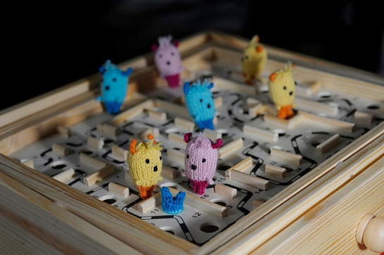 Tiny knitted monsters wander a wooden maze