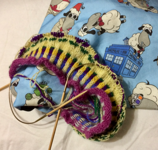 First two inches of a stranded colourwork hat. It's resting against a new project bag by Erin Lane, decorated with knitting sheep dressed as the various incarnations of Dr. Who.